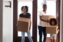 Excited Black Family With Kid Girl Entering Big Modern House Holding Boxes On Moving Day, Happy Parents And Child Daughter Standing In Hallway Looking Around, Tenants Welcome To New Home Concept
