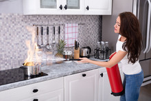Woman Extinguishing Burning Cooking Pot
