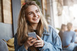 Girl making up funny congratulation, wanting to send it via messages to friend, using brand new smartphone, sitting in cozy and popular city cafe, gazing aside with dreamy pleasant smile