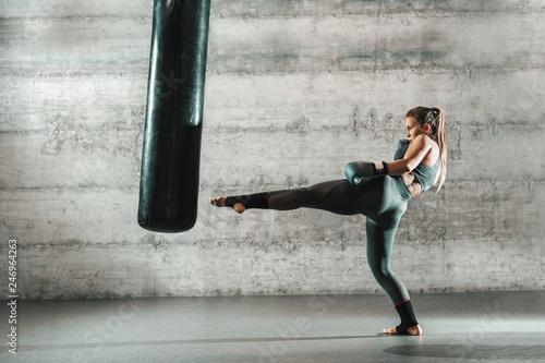 Cuadros en Lienzo  Caucasian woman in sportswear and with boxing gloves kicking bag in the gym