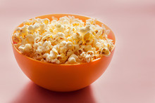 An Orange Bowl With Popcorn Isolated On Pink Background