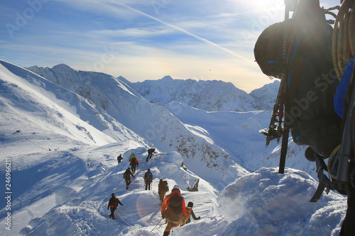 Spoed Fotobehang Alpinisme Tied climbers climbing mountain with snow field tied with a rope with ice axes and helmets