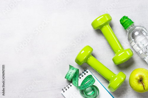 Photo Dumbbells, measuring tape, water and apple top view.