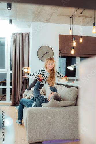 Fototapeta Cute small daughter in a striped sweater feeling amazing obraz na płótnie