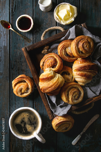 Fototapeta Variety of homemade puff pastry buns cinnamon rolls and croissant served with coffee cup, jam, butter as breakfast over dark plank wooden background