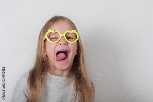 Photo  Portrait of funny naughty little girl in glasses making faces at camera, shows tongue