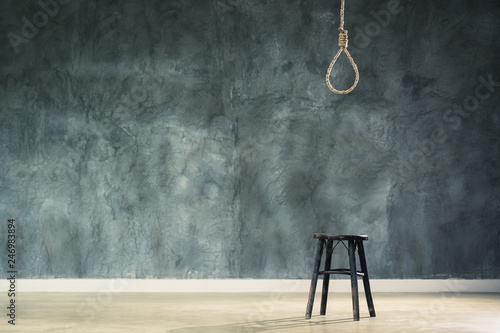 Fototapeta The old chair with the noose hanging at above with space of concrete wall at bac