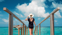 Back View Of Young Woman On A Wooden Pier On A Amazing Background Of Blue Sea And Sky.