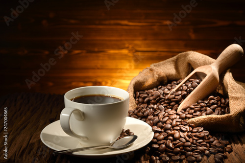 Door stickers Cafe Cup of coffee and coffee beans on old wooden background