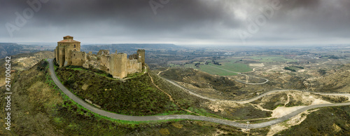 Aerial panorama view of the ruined medieval abandoned Montearagon castle, namesake of the famous kingdom on a bare mountain top near Huesca, Aragon province Spain with stormy cloudy sky