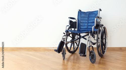 Valokuva  Empty wheelchair in a white room.