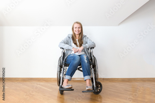 Fotografie, Obraz  Happy invalid woman is sitting on a disability chair in a white empty room