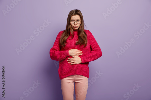 Fotografie, Obraz Sad woman touches belly, feels pain after eating fast food, suffers from disorde