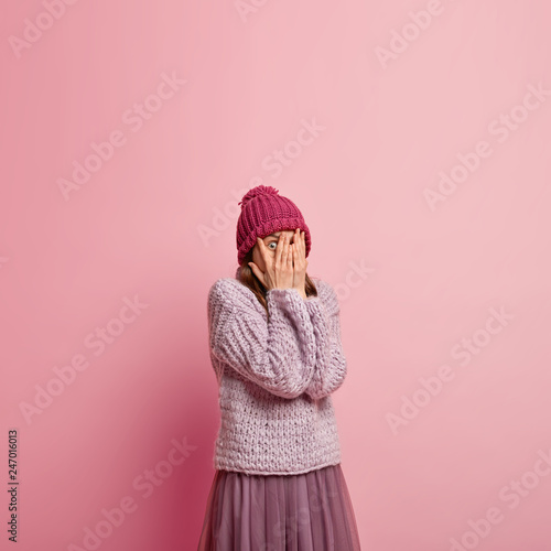Fotografía  Beautiful shocked woman covers face with palms, peeks through fingers, dressed i