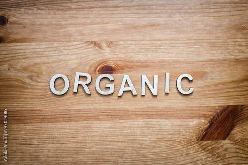 The word organic being spelled by wood letters on a wood surface Wallpaper Mural