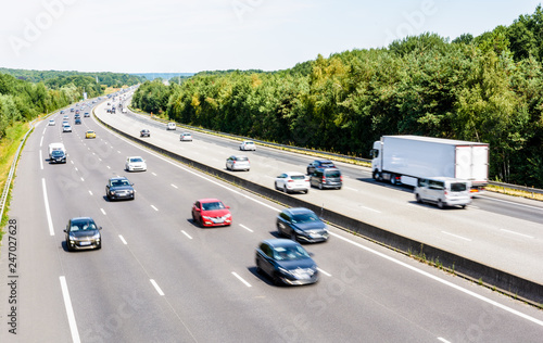 Fotomural Heavy but fluid traffic on the eight-lane A10 highway in France in the direction of Paris by a hot summer day with cars, vans, trailers and semitrailer truck driving