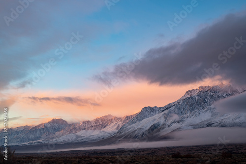 pink sky clouds over snowy mountain range at sunrise