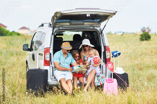 Vacation, Travel - family ready for the travel for summer vacation. suitcases and car route. People with map in hands planning road trip. travel concept. traveler.