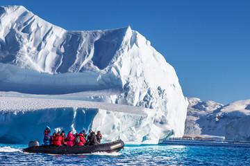 Turisti koji sjede na zodijačkom brodu i istražuju ogromne sante ledenih bregova