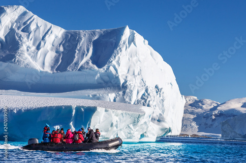 Tourists sitting on zodiac boat, exploring huge icebergs driftin