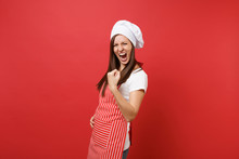 Housewife Female Chef Cook Or Baker In Striped Apron White T-shirt Toque Chefs Hat Isolated On Red Wall Background. Happy Expressive Woman Doing Winner Gesture, Saying Yes. Mock Up Copy Space Concept.
