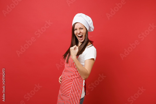 Fotografia Housewife female chef cook or baker in striped apron white t-shirt toque chefs hat isolated on red wall background