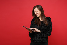 Portrait Of Stunning Joyful Young Woman In Black Fur Sweater Using Tablet Pc Computer Isolated On Bright Red Wall Background In Studio. People Sincere Emotions, Lifestyle Concept. Mock Up Copy Space.