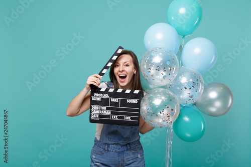 Fotografia, Obraz Funny woman with opened mouth hold classic black film making clapperboard celebrating with colorful air balloons isolated on blue turquoise background