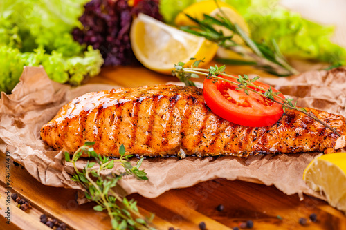 Fototapeta Grilled salmon with tomato and herbs on wooden board obraz