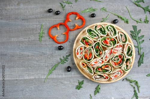 Fototapeta Kolorowe roladki z tortilli, rukoli, papryki, wędzonego łososia lub szynki parmeńskiej obraz