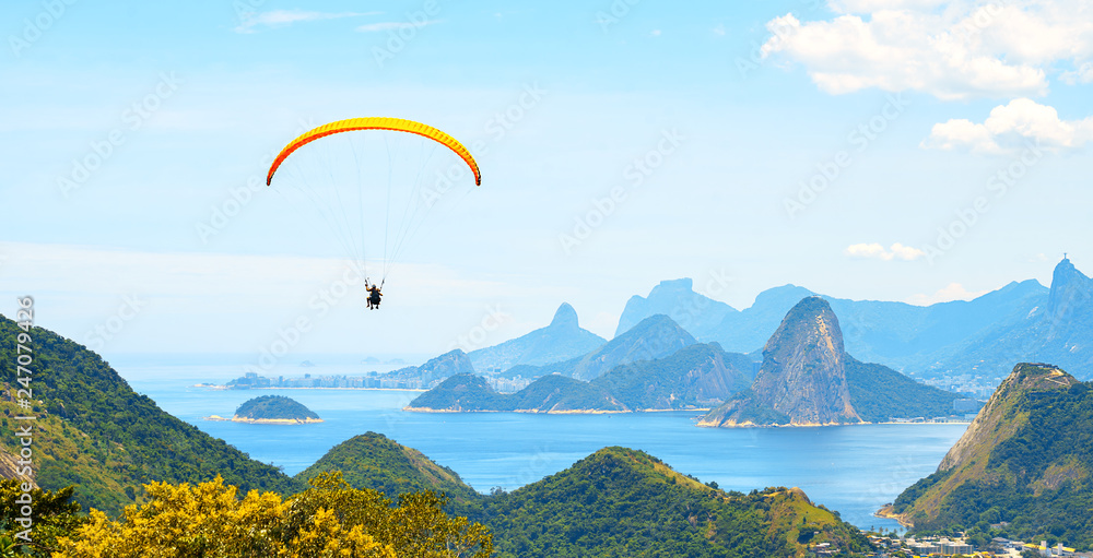 Fototapety, obrazy: A colorful parachute with skydiver on sunny blue sky background. Active lifestyle. Extreme sport. Concept of holidays, vacation, tourism. horizontal. Aerial view of Rio de Janeiro with turquoise water