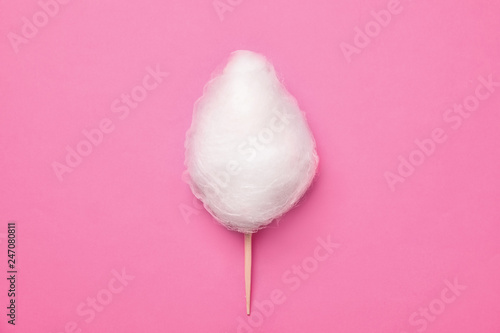 Stick with yummy cotton candy on color background, top view