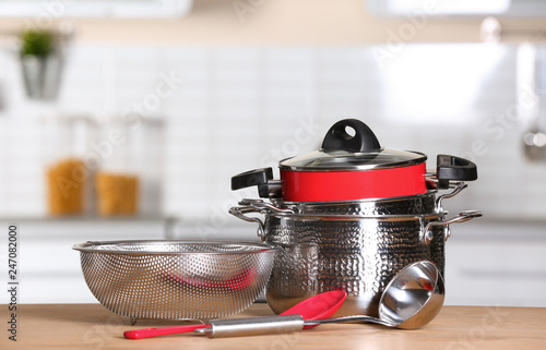 Set of clean cookware and utensils on table in kitchen