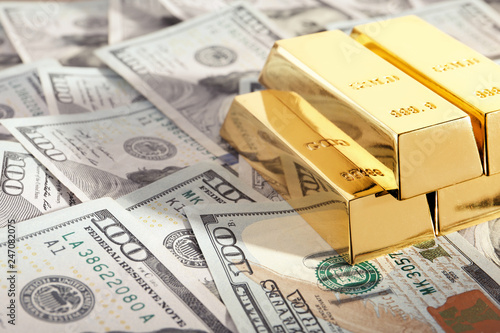 Fotografie, Obraz  Shiny gold bars on pile of dollar bills. Space for text