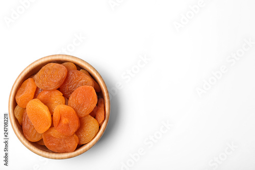 Wooden bowl of dried apricots on white background, top view with space for text. Healthy fruit
