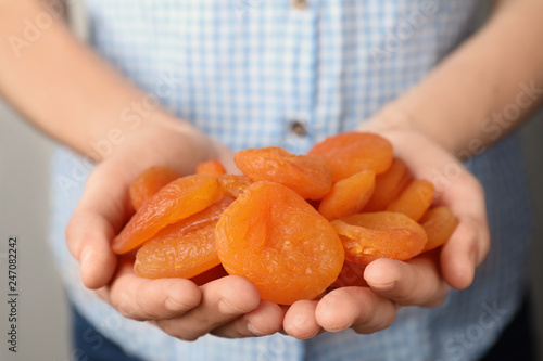 Woman holding handful of dried apricots, closeup. Healthy fruit