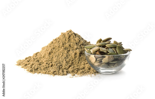 Pile of fresh flour and bowl with pumpkin seeds isolated on white