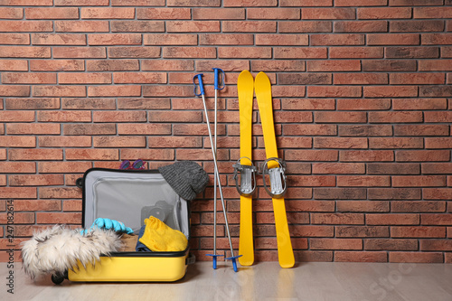 Suitcase with clothes, camera and skis on floor against brick wall, space for text. Winter vacation