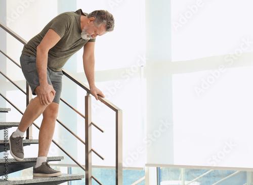 Starszy mężczyzna cierpi na ból kolana w pomieszczeniu. Miejsce na tekst
