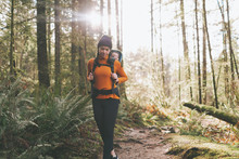 A Young Woman Hiking Through The Forest With A Baby On Her Back.