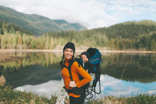 A Mother Hiking In The Canadian Mountains With Her Baby On Her Back.
