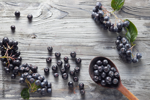 Freshly picked homegrown aronia berries on wooden table