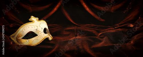 Photo of elegant and delicate gold, white venetian mask over dark velvet and silk background.