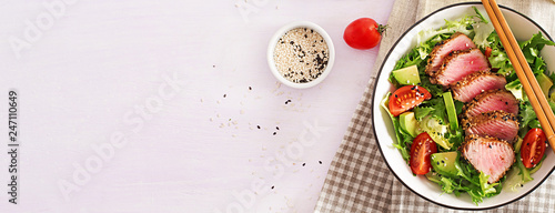 Tuna salad. Japanese traditional salad with pieces of medium-rare grilled Ahi tuna and sesame with fresh vegetable on a bowl. Authentic Japanese food. Top view. Banner