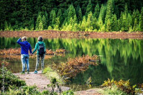 Foto  Young couple in colorful sweatshirts is standing in front of the volcanic lake on Azores Islands