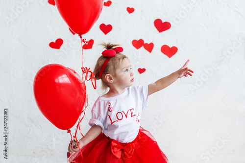 фотография Pretty cute baby girl holding heart-shaped balloons on saint valentine's day