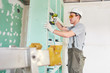 Room repair. Building. Worker fastens drywall with a screwdriver
