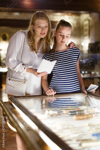 Fotomural Woman visitor with daughter looking to art objects under glass  with guide book