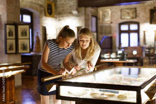 Girl with woman looking with interest at art objects under glass in museum Tableau sur Toile
