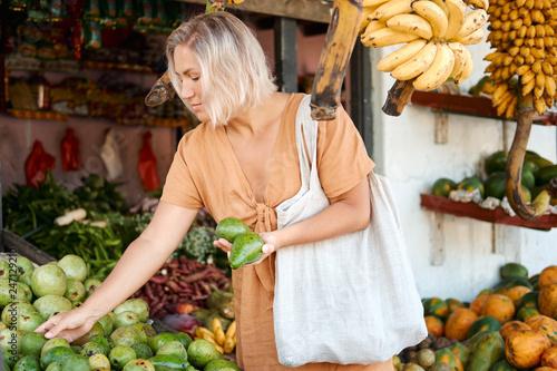 Plakat Kobieta Kup organiczne awokado na tropikalnym rynku wiejskim
